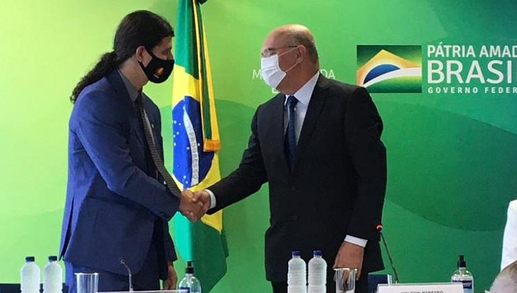A imagem mostra dois homens, apertando as mãos. Atrás o banner verde e amarelo com os dizeres