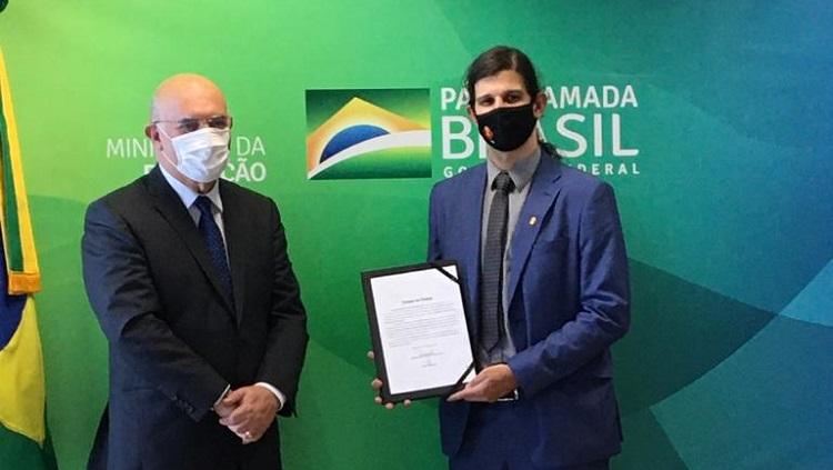 A imagem mostra dois homens, à direita, Danilo segura o documento de posse ao lado do Ministro da Educação