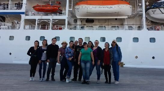 A foto mostra grupo de alunos e professor em frente ao transatlântico no Porto de Rio Grande