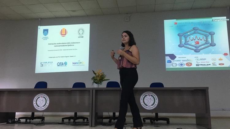 A foto mostra a mestranda Nichole Osti Silva em pé, segurando um microfone, apresentando seu trabalho de pesquisa, que aparece projetado ao fundo da imagem.