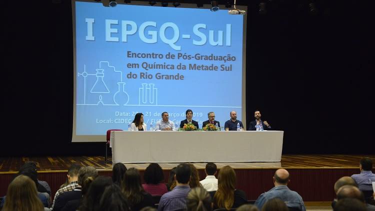 Em primeiro plano pessoas olhando para a mesa que está a frente. Mesa comprida em cima de um palco composta por cinco homens e uma mulher. Ao fundo identificação do evento.