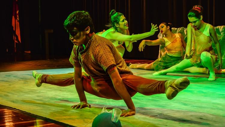 Imagem mostra menino em detalhe, realizando um movimento de abertura total das pernas no sentido horizontal enquanto apoia ambas mãos no chão