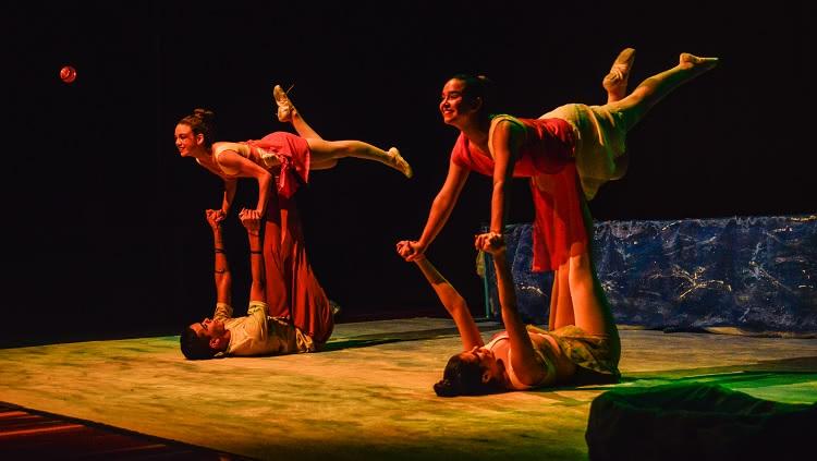 Imagem mostra dois bailarinos, de costas para o chão, segurando no alto de seus braços outras duas dançarinas