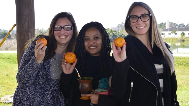 Três mulheres sorrindo mostrando as bergamotas em suas mãos