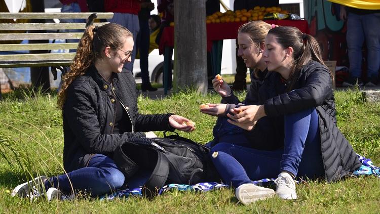 Três mulheres sentadas na grama sorrindo entre si