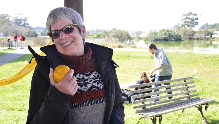 Mulher segurando bergamota na mão e sorrindo