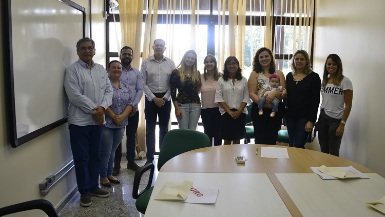 A foto mostra os quatro novos servidores, a reitora Cleuza Dias e os representantes de cada unidade dispostos um ao lado do outro.