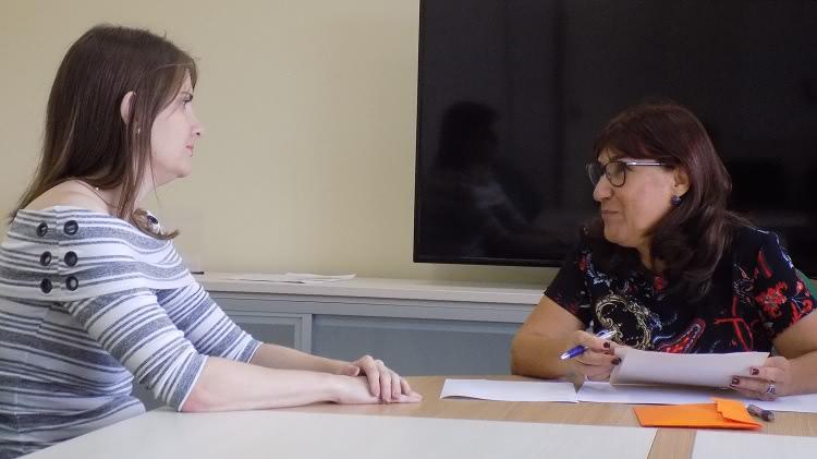 A imagem mostra duas mulheres, uma olhando para a outra. À esquerda, a nova servidora empossada. Ela está com as mãos sobre uma mesa de reuniões. À direita, a reitora, com papeis à sua frente na mesa e segurando uma pasta e uma caneta nas mãos.