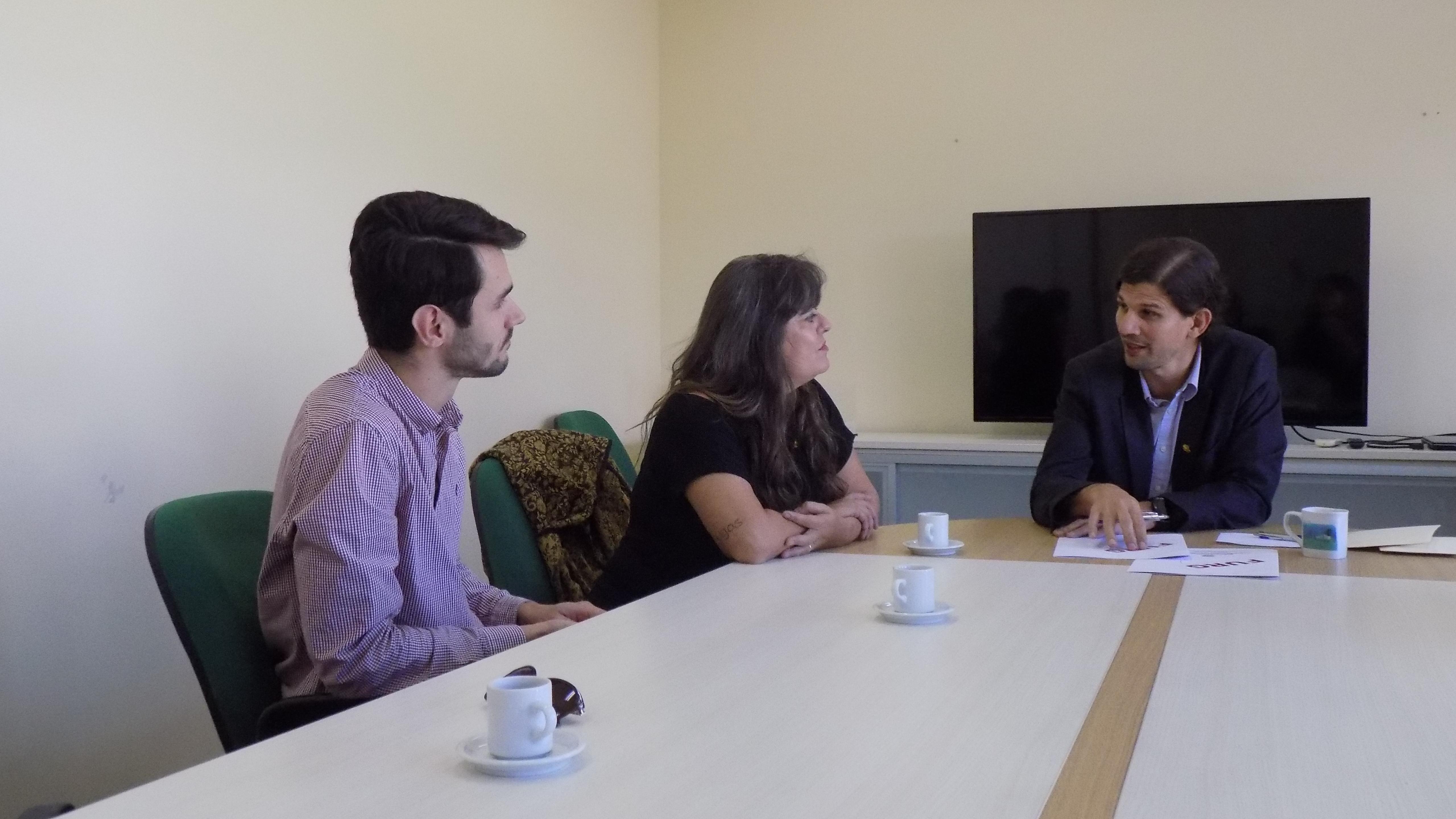 Três pessoas sentadas a mesa, dois lado a lado e um a frente. São dois homens e uma mulher. Mesa branca, cadeiras verdes. Em cima da mesa tem papéis, xícaras e caneta.