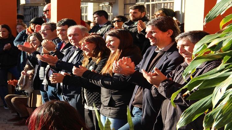 A imagem mostra grupo de pessoas na lateral da foto sorrindo e aplaudindo.