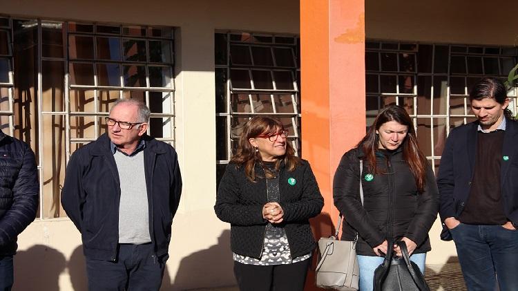 A foto mostra grupo de pessoas em pé, lado a lado.