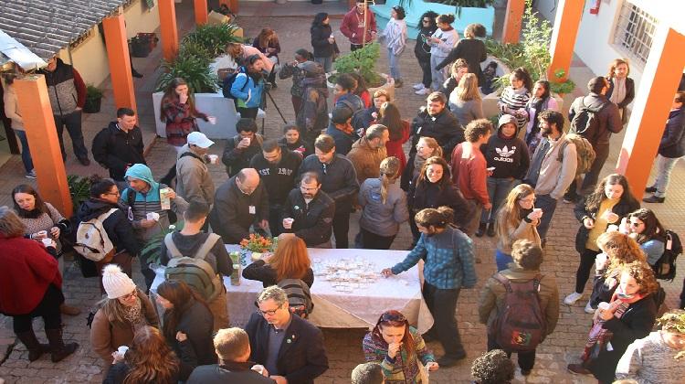 Imagem mostra grupo de pessoas em volta da mesa.