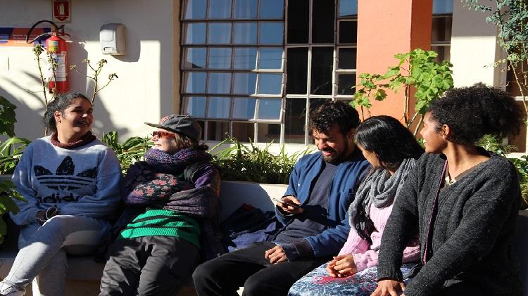 Foto mostra grupo de pessoas sentadas.