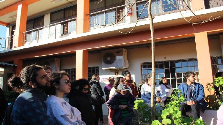 Imagem mostra pessoas em pé olhando para frente.