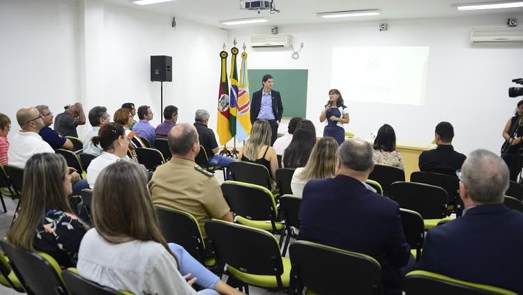 Em pé, o vice-reitor Danilo Giroldo fala ao público sentado em cadeiras no interior da sala Estuários, no Cidec-Sul. Em um telão atrás dele, há uma imagem onde se lê