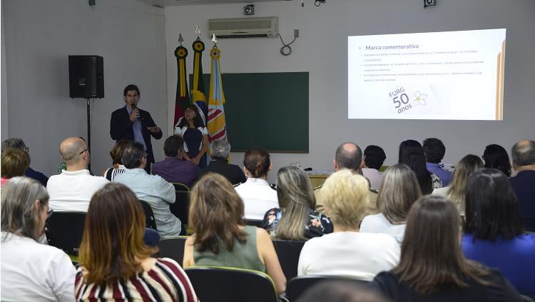 A reitora da FURG, Cleuza Maria Sobral Dias, e o vice-reitor Danilo Giroldo, ambos em pé, falam ao público sentado em cadeiras no interior da sala Estuários, no Cidec-Sul.