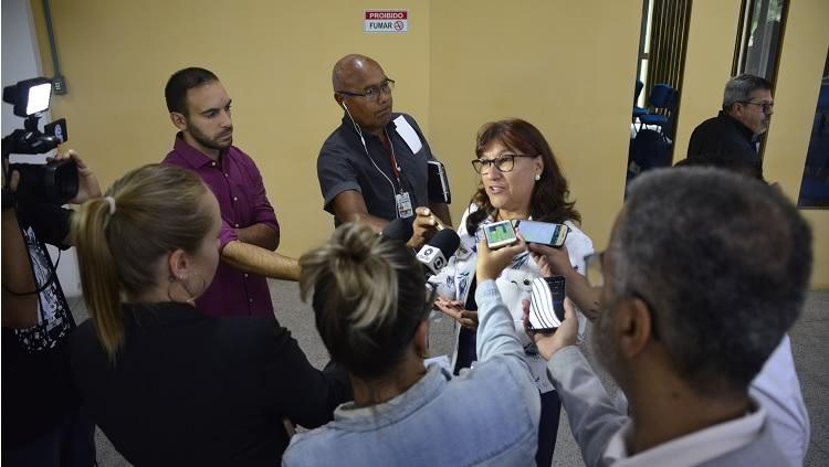 No centro da foto, a reitora da FURG, Cleuza Maria Sobral Dias, está rodeada por repórteres que carregam microfones e smartphones. À esquerda, um cameraman aponta a câmera para a reitora.