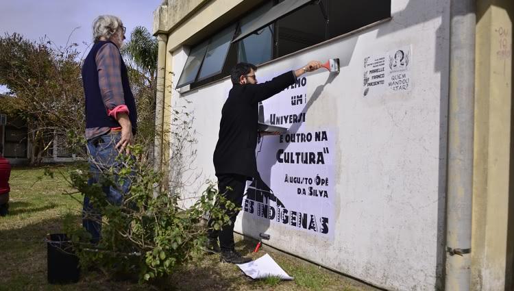 A imagem mostra duas pessoas realizando uma intervenção artística por meio de colagens em uma parede