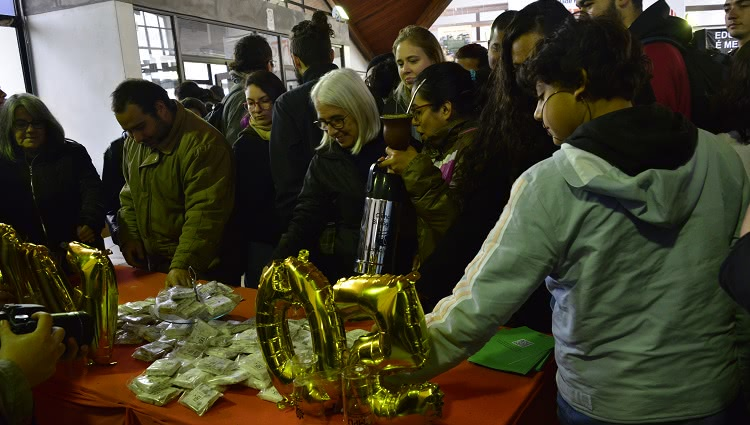 A imagem mostra estudantes retirando as palhas italianas distribuídas em uma mesa no CC