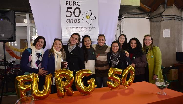 A imagem mostra pessoas na frente de uma mesa com balões comemorativos
