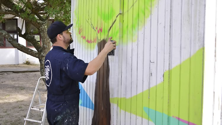 A imagem mostra uma pessoa grafitando uma parede
