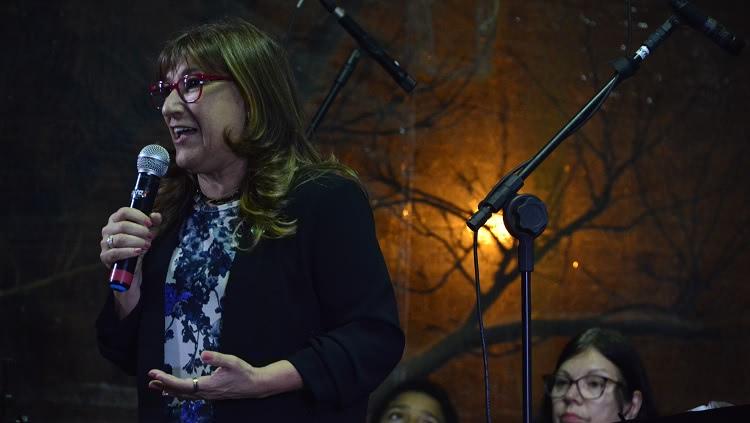 Em pé, com o microfone à mão, a reitora Cleuza Dias aparece de perfil, falando