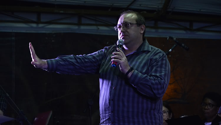 Um homem aparece no palco, com o microfone à mão.