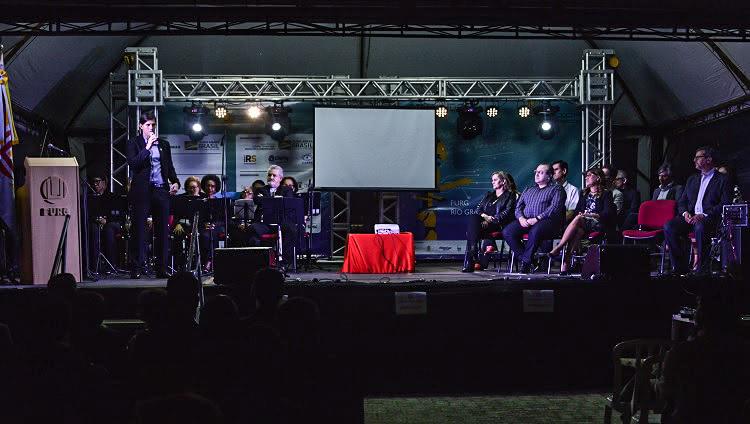 A foto foi feita à noite, num palco iluminado. Há várias pessoas sentadas em um homem em pé, com o microfone à mão