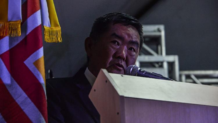 Um homem aparece atrás de um púlpito, falando ao microfone. O plano é fechado no rosto dele. Ao fundo, aparece uma parte da bandeira da FURG.
