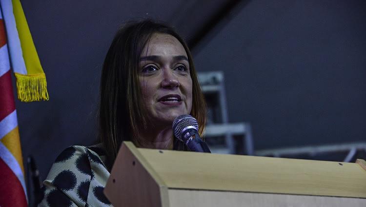 Uma mulher aparece atrás de um púlpito, falando ao microfone