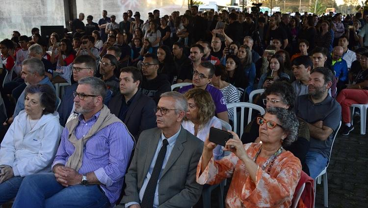Na imagem aparece várias pessoas sentadas: é o público do evento, olhando em direção ao palco, que não aparece na foto