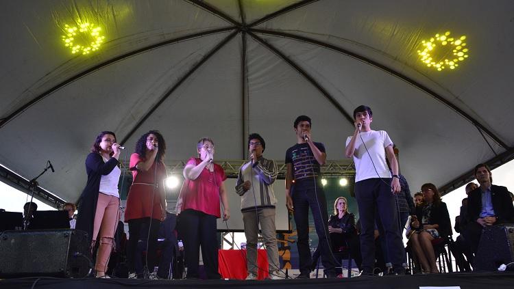Seis pessoas aparecem no palco, cantando. Todas estão com microfone na mão. À esquerda estão três mulheres, à direita três homens.