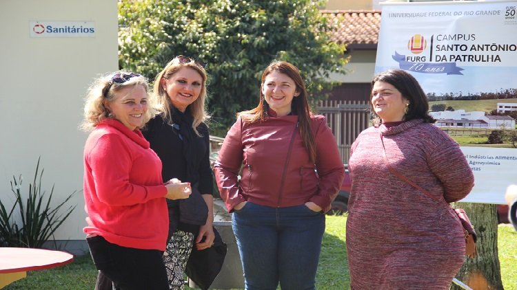 Na imagem mostra quatro mulheres em pé olhando em direção a foto.