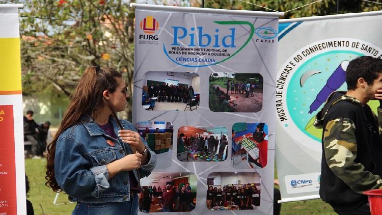 A foto mostra um banner do Pibid da FURG e uma mulher próxima a ele olhando para o lado.