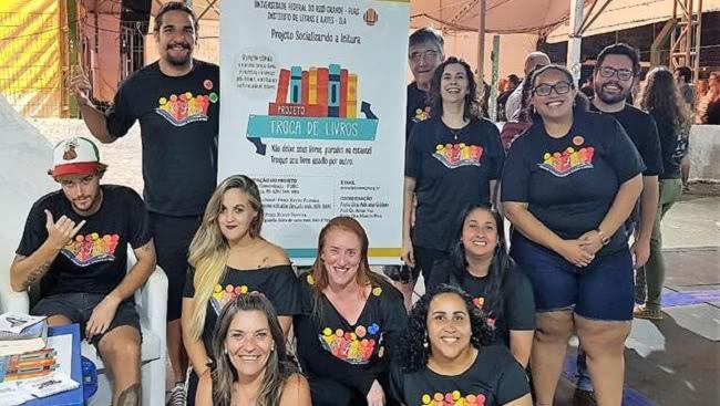 Grupo de professores e voluntários em frente ao estande do Troca de Livros na 46ª Feira do Livro da FURG.