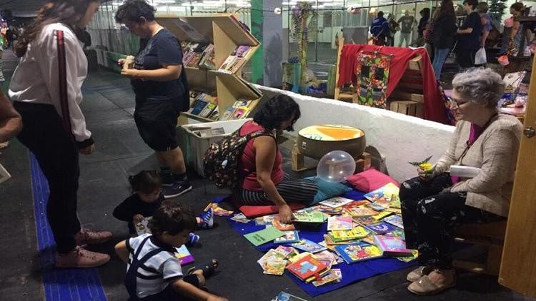 Crianças, uma senhora e outros visitantes em frente ao estande do Troca de Livros na 46ª Feira do Livro da FURG.