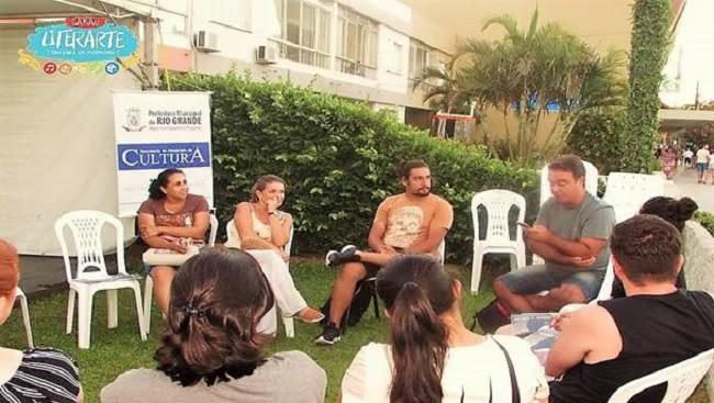 Roda de conversa com os voluntários do programa em evento ao ar livre.