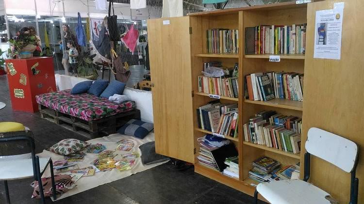 Um espaço montado na feira do livro, com um armário com as portas abertas e, em seu interior, muitos livros. Ao lado do armário há um pano no chão e, sobre ele, almofadas e livros. Ao redor do pano, uma cadeira e um banco. Próximo também há um sofá feito de pallets, com almofadas.