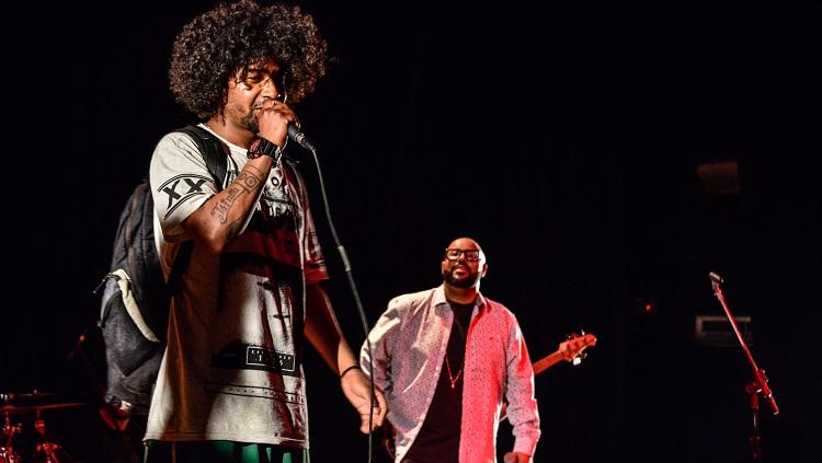 O terceiro rapper freestyle segurando o microfone enquanto é assistido pelos integrantes da banda