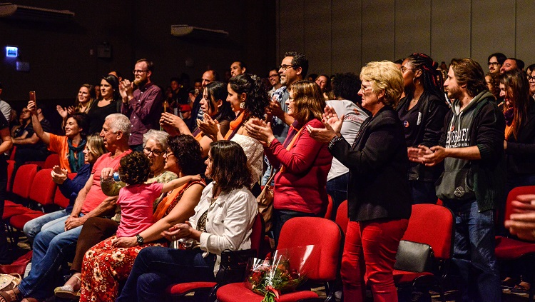 A foto mostra as pessoas da plateia, umas em pé e outras sentadas,assistindo o show