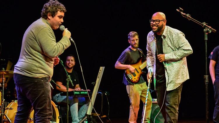 O estudante Fernando Neto no palco segurando o microfone e ao lado dele o cantor Vagnotreta