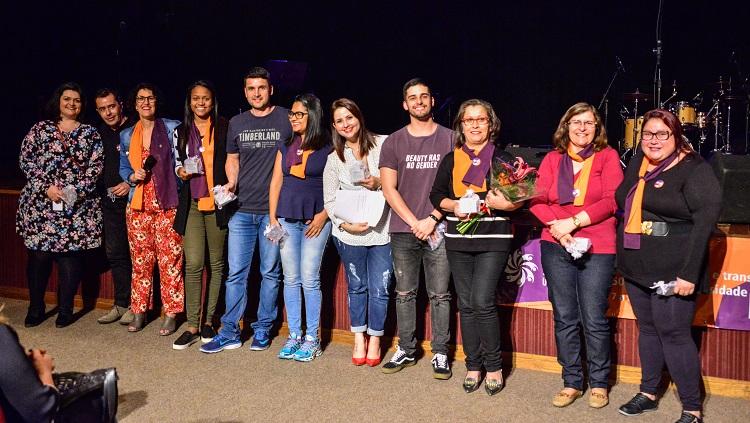 Na foto, um grupo de 11 pessoas aparecem lado a lado na frente do palco segurando as placas de homenagem entregues