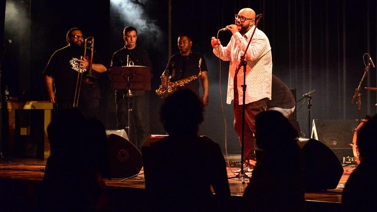 A foto mostra o vocalista Vagnotreta cantando em cima do palco e sua banca disposta ao fundo com baixa iluminação