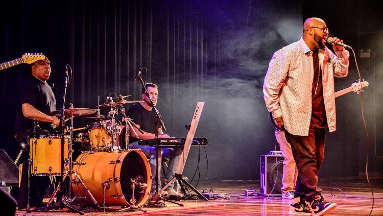 O baterista e o tecladista da banda aparecem na foto juntamente com o vocalista Vagnotreta