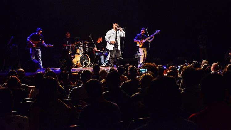 A foto mostra o cantor Vagnotreta no palco iluminado pela luz cênica quanto as pessoas o olham