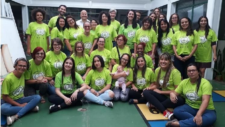 Um grupo de 32 pessoas aparece na foto, todos olham para a câmera. As pessoas ao fundo estão em pé, as mais à frente, sentadas no chão. A maior parte são mulheres, uma delas segura um bebê ao colo. Todos usam camisetas verdes do projeto cirandar.