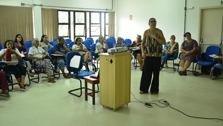A assistente social da Proexc, Fernanda Fonseca, palestra em pé, em frente a um grupo de mulheres sentadas.