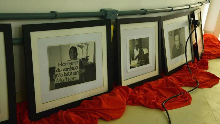 Alguns quadros com fotografias de mulheres estão colocados um ao lado do outro, apoiados na parede, em cima de um tecido vermelho. As fotografias são em preto em branco. Em uma delas, uma mulher segura um cartaz que diz