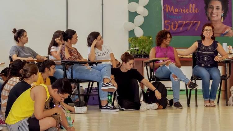 Grupo de mulheres sentadas em roda, algumas em cadeiras e outras no chão. No fundo, uma faixa com a foto de Marielle Franco e o número da sua candidatura nas eleições do Rio de Janeiro, 50777.