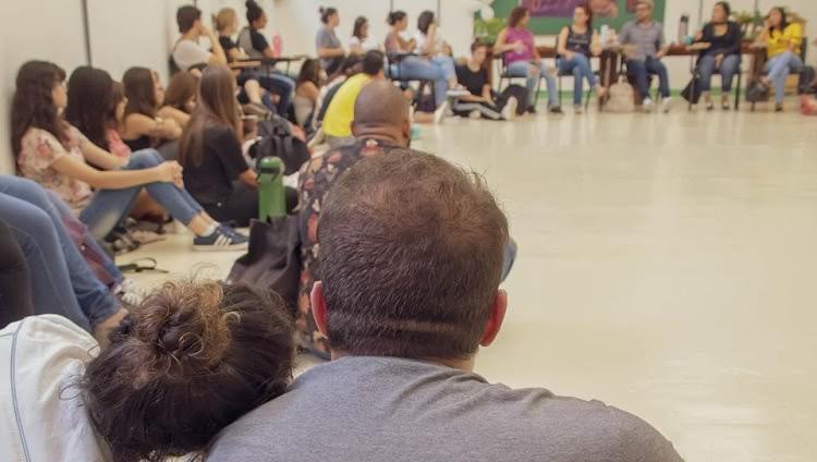 Grupo de aproximadamente 30 pessoas sentadas em roda. Algumas em cadeiras, outras no chão. Mais próximo à câmera, de costas, uma mulher apoia a cabeça no ombro de um homem ao seu lado.